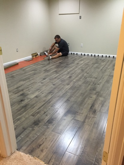 Our first diy project laminate flooring in ben s for Best flooring for basement family room